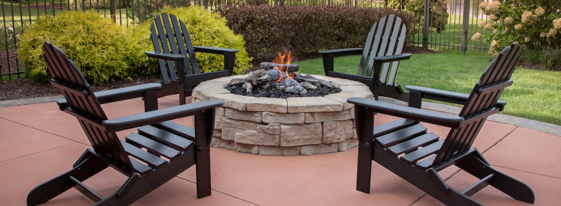 Black Adirondack Chairs around a fire pit